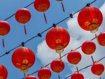 Lanternas vermelhas chinesas de suspensão em um templo chinês contra um céu azul Foto de Stock