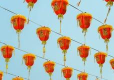 Lanternas vermelhas chinesas que penduram no céu azul Imagem de Stock Royalty Free