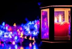 Lanterne avec la bougie brûlante sur le fond du bokeh sous forme d'arbres de Noël Images stock