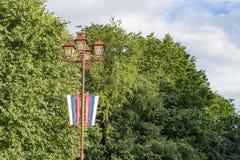 Lanterne avec un drapeau sur le fond du feuillage vert photo stock