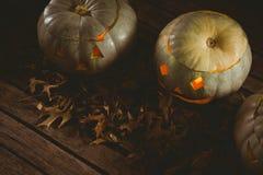 Lanterne bianche illuminate della presa o con le foglie di autunno sulla tavola Fotografie Stock Libere da Diritti