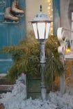 Lanterne blanche à l'entrée à une maison privée en hiver patins accrochant sur la poignée de porte, à feuilles persistantes dans  photos stock