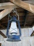 Lanterne bleue rouillée accrochant dans un hangar Photos libres de droits