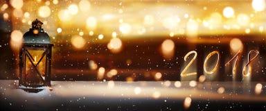 Lanterne brûlante dans la neige pendant une nouvelle année Images stock