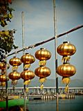 Lanterne cinesi dorate sotto cielo blu Fotografia Stock