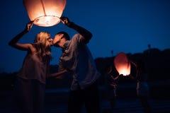 lanterne de baiser et de lancement de jeunes couples de ciel sur la plage de rivière photographie stock