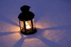 Lanterne de bougie dans la neige Image stock