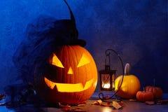 Lanterne de cric de tête de potiron de Halloween avec le chapeau de jeune mariée dans la grange foncée Photo libre de droits