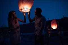 lanterne de lancement de ciel de jeunes couples heureux sur la plage de rivière photos libres de droits