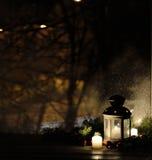 Lanterne de Noël avec des chutes de neige, bougies, vue de la fenêtre sur la rue de nuit Images stock