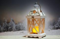 lanterne de Noël et sapins neigeux à l'arrière-plan Image stock