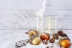Lanterne de Noël sur la neige avec des glands et des feuilles de chêne Photos stock