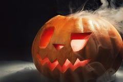 Lanterne de potiron de Halloween avec les feuilles sèches avec les yeux brûlants images libres de droits