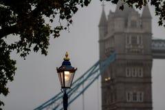 Lanterne de rue contre le pont de tour en brouillard profond de matin Londres, R-U photographie stock libre de droits