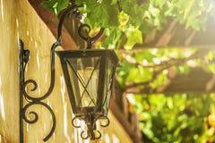 Lanterne métallique de vieux vintage sur le mur en béton avec l'arbre vert au fond Photo stock