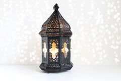 Lanterne marocaine et arabe foncée ornementale sur la table blanche Bougie brûlante, lumières éclatantes de bokeh Carte de voeux  Photographie stock