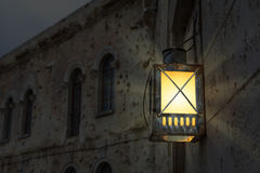 Lanterne rougeoyante lumineuse illuminant le mur d'une construction antique image libre de droits