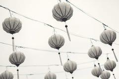 Lanternes asiatiques blanches multiples accrochant dans le ciel photographie stock