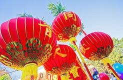 Lanternes chinoises dans le tissu rouge avec les ornements d'or Images stock
