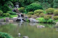 Lanternes et cascade en pierre japonaises dans Koi Fish Pond à Photographie stock libre de droits