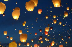 Lanterns, balloons fly to heaven. Flying with the intention of peace in the world. Yellow-orange lanterns against the background of the blue sky. Each balloon Stock Photos