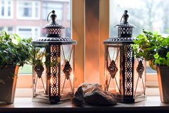 Lanterns with burning candles in window Royalty Free Stock Images