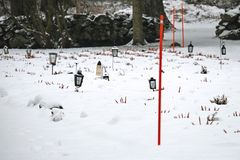 Lanterns with candles at the cemetery grave yard covered with snow in winter royalty free stock image