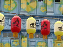 Lanterns in Chinatown, Singapore. A row of lanterns with Chinese characters hanging before a shop-house in Chinatown, Singapore. The front facade of the shop royalty free stock image