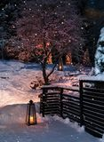 Lanterns in Christmas snowfall garden. Lanterns in snowy winter garden yard snowfall royalty free stock photography