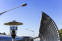 Lanterns near the bus stop and the sound-absorbing tunnel. Metal structure and screens, glass, light. Modern technology in the city of Warsaw, Poland Royalty Free Stock Photo