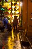 Hoi An, Vietnam - June 2017: night life on street during rainy night in lantern lit Hoi An, Vietnam. Lanterns and night life on street during rainy night in Stock Photos
