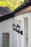Lanterns on old wall, perspective view. Perspective view of two wall lanterns on old house, taken in Mother Shipton's Park, Knaresborough, North Yorkshire Royalty Free Stock Photo