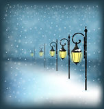 Lanterns stand in snowfall on blue Stock Image
