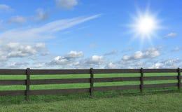 Lantgård Fält med gräs och ett staket Royaltyfria Bilder