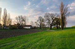 Lantgård för vårlandskapvisning på bygd på skymning Arkivfoton