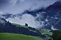 Lantgård och pinjeskog i de österrikiska fjällängarna med mörka dramatiska moln över en brant skogsbevuxen kant i bakgrunden arkivfoton
