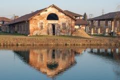 Lantgård reflekterad i vattnet Arkivbild