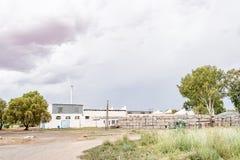 Lantgårdbyggnader bredvid den Riet floden Arkivbild