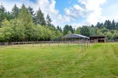 Lantgårdfält med den tomma hästladugården royaltyfri fotografi