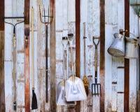 Lantgårdhjälpmedelhögaffel och två skyfflar mot gammalt träväggbruk arkivfoto