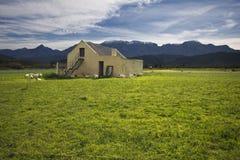 Lantgårdhus med berg och gröna fält Arkivbild