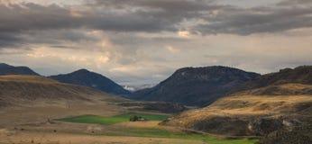 Lantgårdland i en dal med berg royaltyfri fotografi