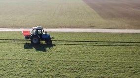 Lantgårdmaskineri som besprutar insekticid till det gröna fältet, jordbruks- naturlig säsongsbetonad vårbakgrund arkivfilmer