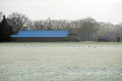 Lantgårdnötkreaturskjul med det djupfrysta taket i lantligt vinterlandskap Fotografering för Bildbyråer