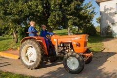 Lantgårdpojkar med traktoren Arkivfoton