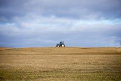 Lantgårdtraktor på öppet skördfält för sned boll Royaltyfria Bilder