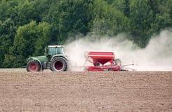 Lantgårdtraktor på fält Arkivbild