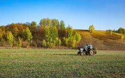 Lantgårdtraktor på fältet i Europa royaltyfri bild