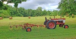 Lantgårdtraktoren med fäst hö krattar framme av för en tid sedan-mejad royaltyfri foto