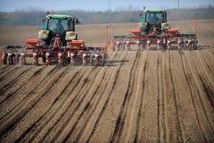 Lantgårdtraktorer som planterar fältet Arkivbilder